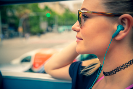 Tourist woman on the bus tour with headphones in ears listening guide, discovering points of interest of Barcelona, active summer vacation in Europe Banco de Imagens