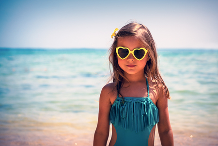 Portrait of a cute little girl on the beach, charming child wearing stylish swimsuit and heart shaped sunglasses, baby fashion, happy summer holidays Banque d'images - 104399212
