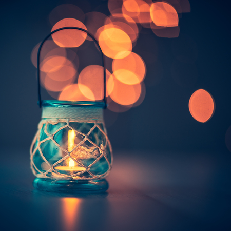 Beautiful vintage candlestick on blurry lights background, antique decor in restaurant interior, romantic candlelight atmosphere
