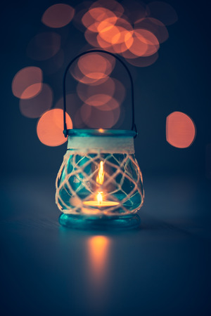 Closeup photo of a retro candle lantern on the table with reflection on it over blurry lights background, romantic evening concept