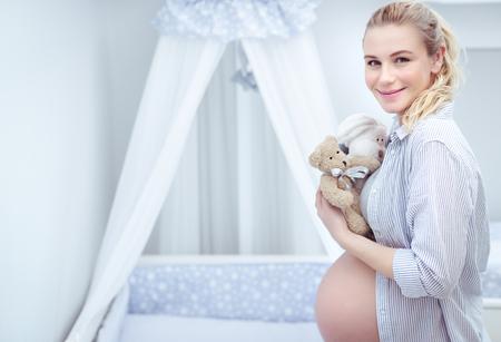 Bella donna incinta in piedi nella stanza del bambino con peluche in mano, decora e fissa tutto nella camera da letto per il suo bambino, cura del comfort del bambino Archivio Fotografico - 107953635