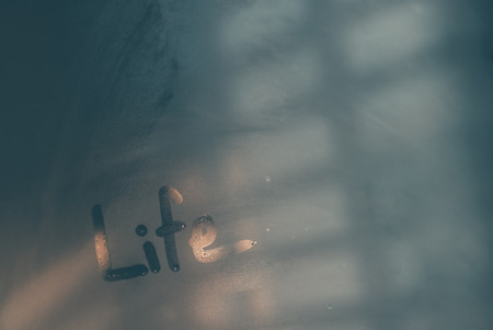Abstract conceptual background, misted-up window glass with written word on it, life concept Reklamní fotografie