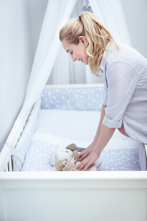 Happy pregnant woman prepares a children's room for her baby, decorating a crib with soft toys, young female enjoying pregnancy time Foto de archivo