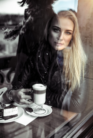 Portrait of a nice but sad woman drinking coffee in the cafe, alone thoughtful beautiful girl in depression, bad mood and unhappiness concept Фото со стока