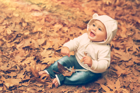 Adorable child sitting on the  ground covered with dry tree leaves in warm autumn day and with wonder looking up to the sun, happy autumnal time