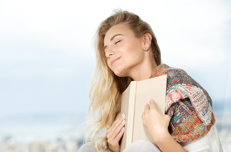 Portrait of a beautiful dreamy woman with closed eyes holding book near the heart, enjoying romantic story, happy quality time at home Stok Fotoğraf - 113030799