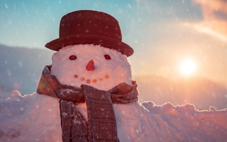 Photo of a cute snowman dressed in a stylish hat and scarf in a snowy frosty evening on a sunset background, happy winter holidays tradition Stock Photo