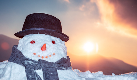 Portrait of a nice smiling snowman outdoors in the evening over sunset sky background, good wintertime tradition, happy winter holidays concept Stock Photo