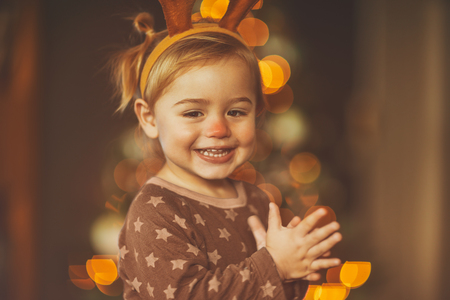 Portrait of a happy little boy wearing festive raindeer horns, Rudolph the red nosed reindeer, cheerful baby clapping of pleasure