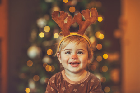 Portrait of a cheerful laughing baby wearing Rudolphs reindeer costume, with pleasure spending Christmas at home near beautiful glowing Christmas tree