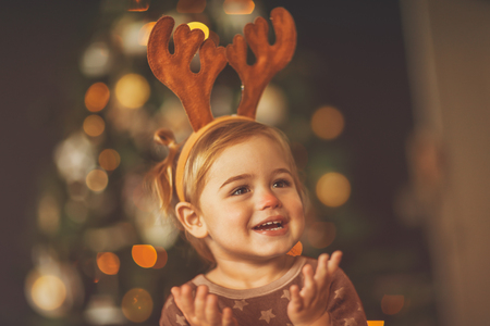 Portrait of a cute little baby boy wearing red nosed rudolph costume, shot over beautiful bokeh lights of the Christmas tree, having fun on the matinee