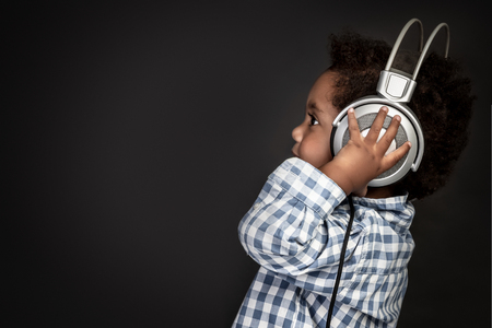 Profile portrait of a little curly African-American baby boy wearing big headphones and listening favourite music over black background, sweet child having fun 版權商用圖片