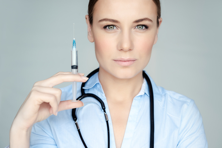 Portrait of a serious woman doctor with syringe isolated on gray background, doctor making anti aging treatment, injections of youth and beauty Banque d'images