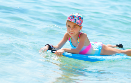 Happy little girl with bodyboard in blue transparent sea, enjoying water sport, having fun in summer camp