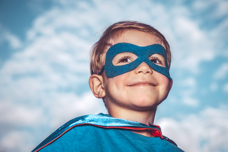 Closeup portrait of a nice little superhero over blue sky background, a cheerful child wearing superman mask and cape, happy childhood concept Foto de archivo