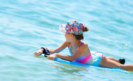 Happy cheerful little girl swimming in the sea on a bodyboard, summertime activities, enjoying summer holidays on the beach resort