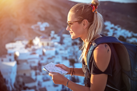 Happy traveler girl is looking to the map, searching the way to walk to beautiful city, which she sees far away in the mountains, active summer vacation with backpack