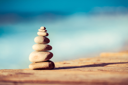 Closeup photo of a pebbles stack on the bridge over sea, spa stones, inner peace and life in balance concept Stock fotó