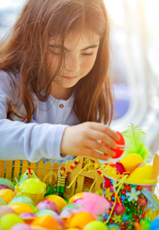 Portrait of a cute little girl playing with colorful eggs, painting and decorating, traditional Easter fun, religious holiday