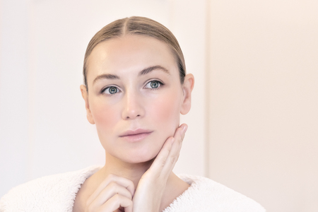Genuine beauty of a young woman with natural makeup, applying anti aging cream, nice female with perfect clear facial skin, beauty and health care concept
