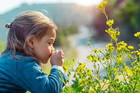 Niño disfrutando del aroma de las flores, con placer con los ojos cerrados oliendo suaves flores silvestres amarillas, disfrutando de la belleza de la naturaleza fresca de primavera