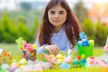 Portrait of a cute little girl enjoying Easter holiday, having fun outdoors and playing with many different colorful eggs, traditional Easter symbol