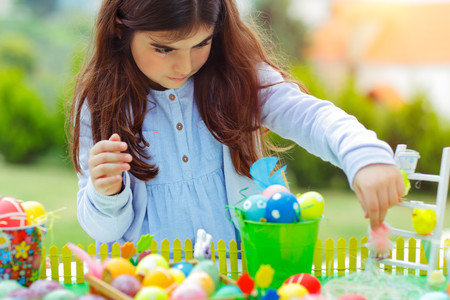 Nice girl playing on Easter holiday with colorful eggs and toys, having fun outdoors on a sunny day, happy childhood
