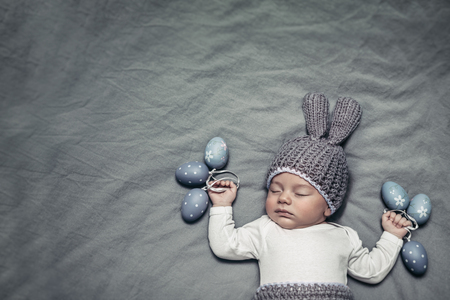 Portrait of an adorable newborn child dressed in a knitted costume of an Easter bunny with stylish decorated eggs, copy space, happy Easter holiday