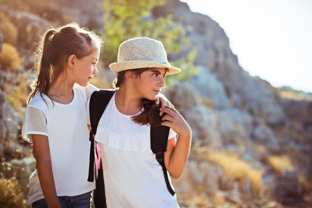 Two school girls with backpacks traveling along mountains, with pleasure spending time in a sportive summer camp Standard-Bild