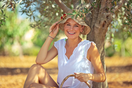 Portrait of a cute happy girl enjoying spring sunny day in the olive garden, resting in the shade of a tree with a picnic basket, weekend in countryside  Фото со стока