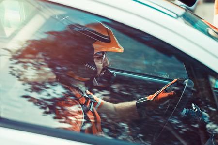 Rallye-Fahrer, der Mann im Helm angespannt und ernsthaft nach vorne schauend, Seitenansicht durch das Autofenster auf den an der Rallye teilnehmenden Rennfahrer, Rennwettbewerb