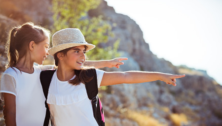 Two happy little girls enjoying excursion to the mountains, with pleasure discovering wild nature, with wonder looking on something and pointing, happy active time in a summer camp Banco de Imagens