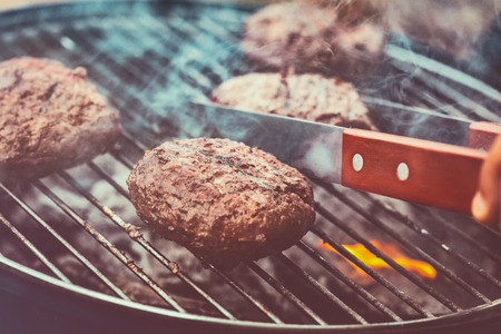Tasty vegan burger on the make, preparation of a veggie patty on the grill, tasty and healthy food, delicious barbecue smoked cutlet, happy summer weekend