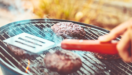 Closeup photo of a tasty vegetarian burger on the grill outdoors, bbq picnic, plant based, healthy delicious food, happy summer weekend Stock Photo