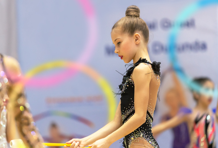 Beautiful little gymnast in the competition dressed in gorgeous black leotard performs an acrobatic moves with a hoop, rhythmic gymnastics school