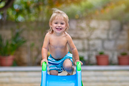 Cute little boy having fun in backyard, with pleasure riding a water slide on the beach resort, happy child enjoying summer holidays Stock Photo - 122538511