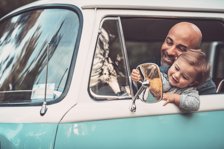 Little boy with father having fun in the car, daddy and son sit in the drivers seat in the van, playing and looking to the rearview mirror, happy family life
