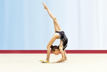 Pequeña gimnasta bailando, movimientos acrobáticos, escuela de gimnasia rítmica, feliz infancia deportiva