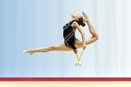 Delightful acrobatic jump with a splits performed by a young gymnast, a girl gymnast dressed in rhinestone embroidered leotard participates in the championship of rhythmic gymnastics