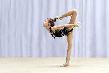 Piccola ginnasta che fa diverse mosse difficili con un club sul palco, partecipando alla competizione di ginnastica ritmica, bellissimo sport per ragazze