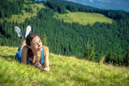 Happy girl chilling in Carpathian mountains, lying down on fresh green grass, enjoying sun rays and clear air, peaceful summer vacation, west Ukraine