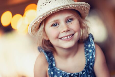 Portrait of nice little smiling girl wearing straw sun hat, enjoying sunny summer holidays, happy healthy childhood