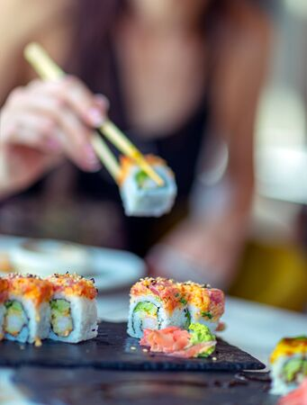 Eating sushi in the restaurant, a woman using chopsticks takes a piece of roll, enjoying tasty and healthy food, traditional Asian cuisine