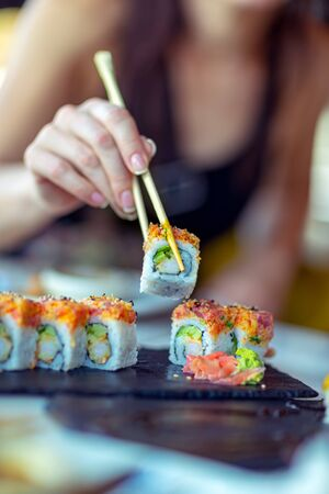 Eating sushi in the restaurant, a woman with a perfect manicure using chopsticks takes a piece of roll, enjoying tasty and healthy food, traditional Asian dish