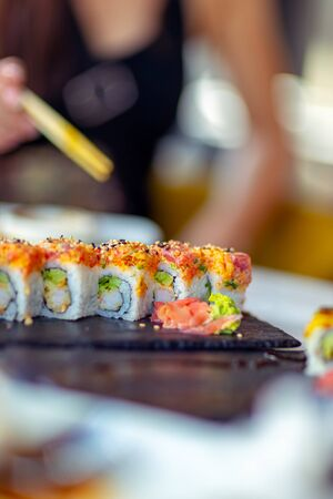 Tasty california roll, woman using chopsticks, eats delicious healthy sushi, enjoying oriental food, having lunch in a sushi bar, an asian restaurant menu