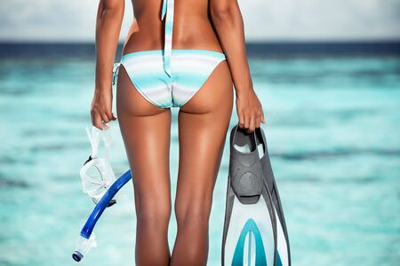 Enjoying water sport, rear view of a young adult girl on the beach Stock Photo