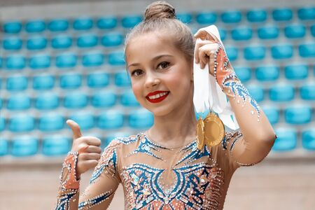 Winner of the rhythmic gymnastics competition, portrait of a pretty little girl holding in hand two gold medal and gesturing by thumbs up a good mood, happy sportive childhood 写真素材
