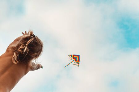 Happy child playing with a kite, child looking up at a multi-colored kite soaring in the sky, happy childhood, enjoying summer holidays