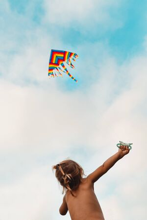 Happy child launches a kite, baby looking up at a multi-colored kite soaring in the sky, happy childhood, kid enjoying summer holidays, photo with copy space, freedom concept