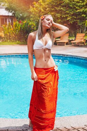 Attractive woman standing near the pool and enjoying bright sun light, with pleasure spending summer vacation on the luxury beach resort of Costa Rica, Central America